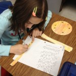 This students is trnsferring the facts that she wrote during her research and writing them onto her sun rays.